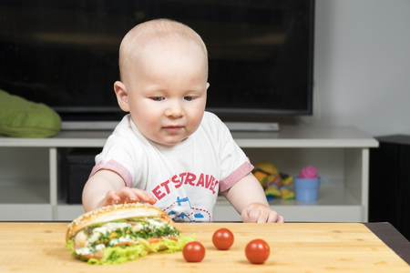 Litlle infant caucasian boy is trying to steal one delicious hotdog with green salad from the table, close to Cherry tomato