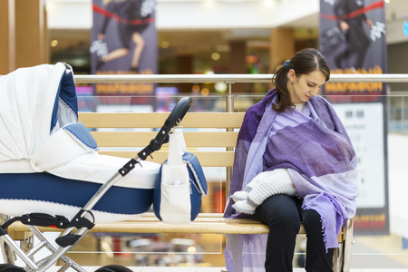 Young european woman with violet stole is breastfeeding her little child close to white baby carriage at public place shopping mall at day time Standard-Bild