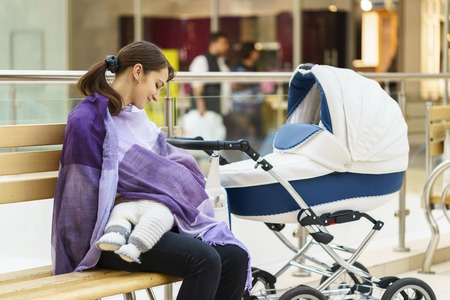 Young european woman with violet stole is breastfeeding her little child close to white baby carriage at public place shopping mall at day time Stock Photo