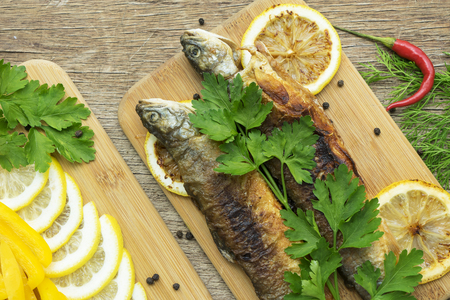 two fried fish of kind of salmon with aromatic herbs and lemon on wooden cutting board