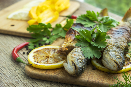 two fried fish of kind of salmon with aromatic herbs and lemon on wooden cutting board Stock Photo - 105342204