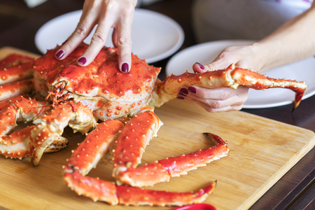 women's hands with red nails is taking leg from big red cooked crab for food