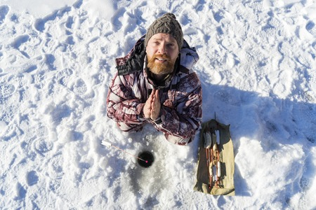 Bearded european sad man is praying and appealing to the god while he getting fail at the winter fishing from ice hole on the river