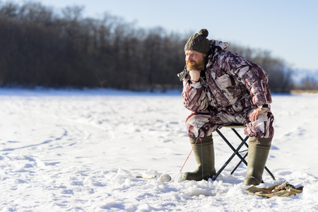 Bearded european sad man is boring while he getting fail at the winter fishing from ice hole on the river