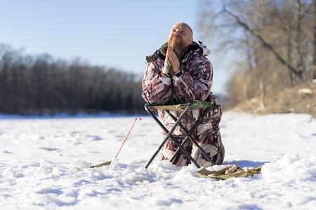Der bärtige europäische traurige Mann betet und appelliert an den Gott, während er beim Winterfischen aus dem Eisloch auf dem Fluss scheitert