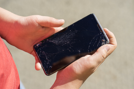 teen is holding some black phone with broken screen after falling down