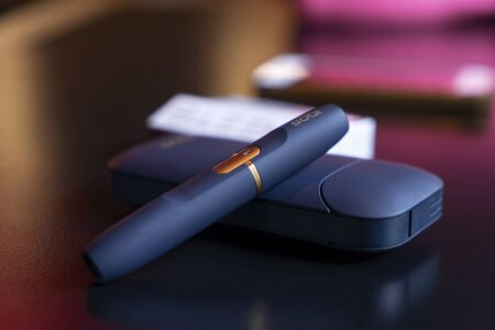 the latest development for harmless, safe, smokeless smoking. black male electronic cigarette Iqos on some table 免版税图像 - 132545045