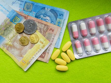 budgets: Ukrainian cheap money for expensive pills close macro photo on green background