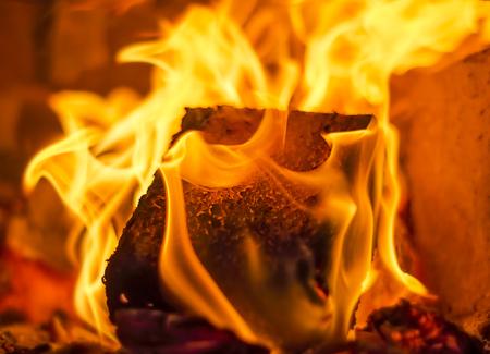 holzbriketts: Brennendes Feuer mit Holzkohle, Holz und Brennstoff Brikett in einem Kamin in einem Landhaus