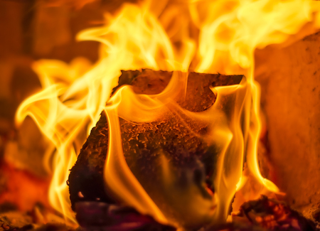 burning house: Burning fire with charcoal, firewood and fuel briquette in a fireplace in a country house Stock Photo