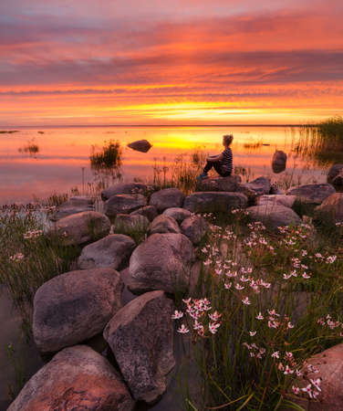 backwater: Fiery sunset with the girl, flowers and stones on the lake Stock Photo