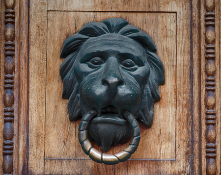 Door handle in the form of a bronze lions head with a ring Stock Photo