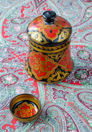 Russian traditional Khokhloma dishes on a red handkerchief. Vintage