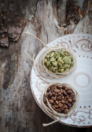 cardamum: Coffee beans and green cardamom on aged wood. Vintage plate