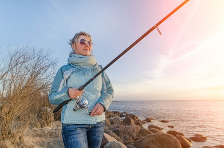 Girl sitting on a rock with a fishing rod. Estonia Stock Photo