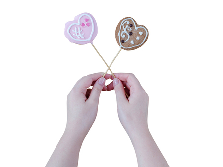gingerbread man: Womans hands holding a Valentine cookies isolated on white background.