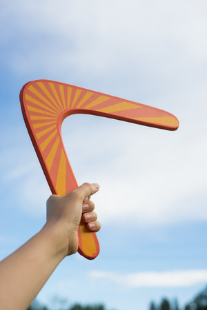 Boomerang in front of a blue sky in woman hand