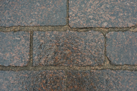 Cobblestone road with wet slippery surface. Close up