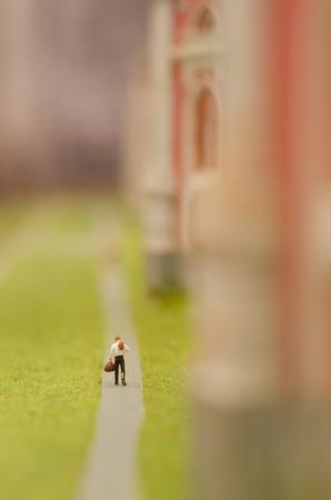 A miniature figure. A man comes with a bag and jacket