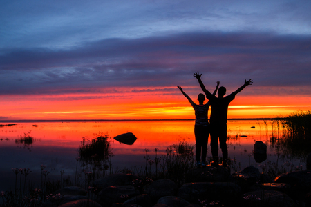 Two happy husband and wife with their hands up at a fiery sunset.