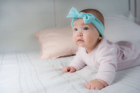 Newborn child wearing a diaper in white sunny bedroom. Newborn child relaxing in bed. Beautiful girl lies a happy smile, great design for any purposes. Happy family. Funny girl.