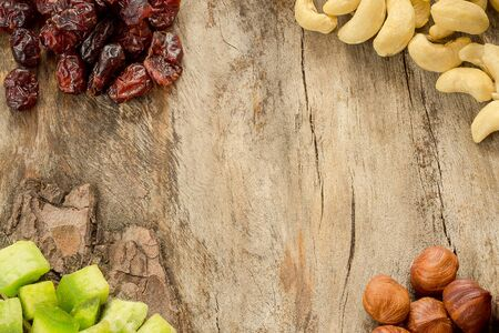 Mix of dried fruits and nuts on aged wood. Copyspace background. Top view. 版權商用圖片