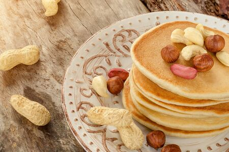Stack of hot pancakes with nuts on the plate. Aged wood