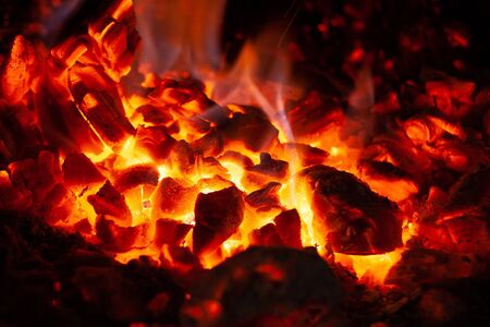 Glowing embers in hot red color, abstract background. The hot embers of burning wood log fire. Firewood burning on grill. Texture of fire fuel briquettes.