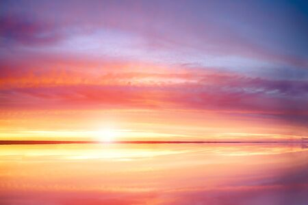 Sunset at the sea, beautiful cloud and sky. Calm sea with sunset sun through. Meditation ocean and sky background. Tranquil seascape. Horizon over the water.
