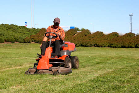 Mature man driving grass cutter in a sunny day photo