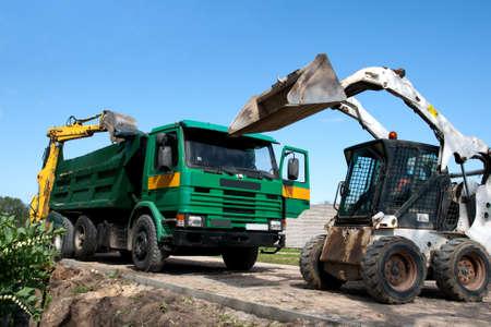 bobcat: Dos excavadoras cargan dumper en el sitio de construcción