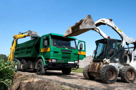 Two excavators loaded dumper at construction site