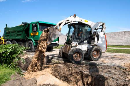 front loader: Trabajo Bobcat Mini en una calle de reconstrucci�n