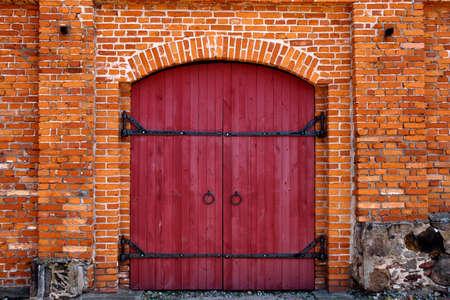 Old Red wooden door in red brick wall  Stockfoto