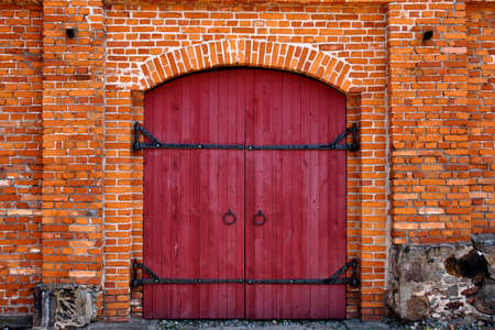 Old Red wooden door in red brick wall  Stock Photo