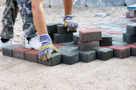 brick paver working on new street Stock Photo