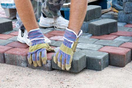 een werknemer die een trottoir van bakstenen