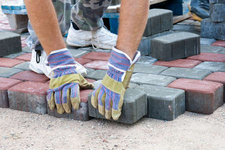 adoquines: un trabajador hizo una acera de ladrillos Foto de archivo