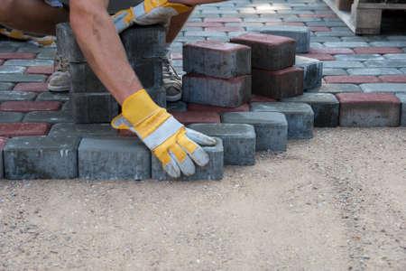 Brukarze hands.Mason jest budowa chodnika. Ręce w żółtych rękawiczkach stanowi warstw cegieł.