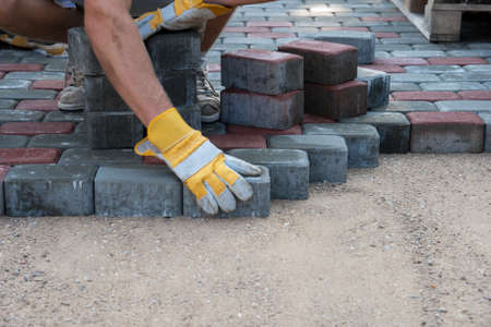 Pavers hands.Mason is building pavement. Hands in yellow gloves lays layers of bricks.