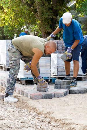 man at work paving stones on new street Stock Photo