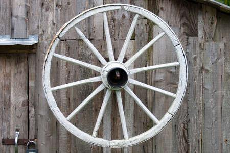 old wood farm wagon: Vintage cartwheel hanging on a wall