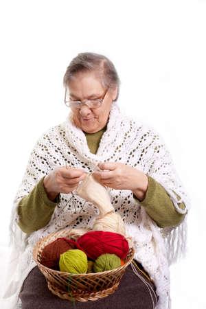 Senior woman knitting isolated on white background photo