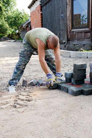 empedrado: Un trabajador de carretera instalado adoquines por un nuevo camino Foto de archivo