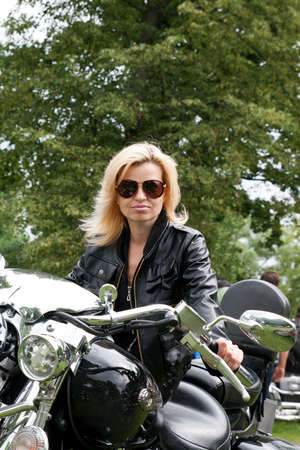Woman in black leather jacket on a motorcycle
