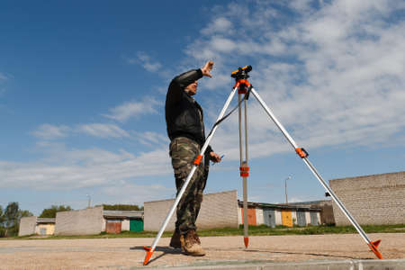 geodesist: Land surveyor working with total station on a construction site. Stock Photo