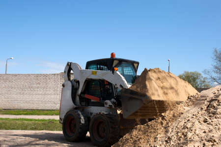 A skid loader doing some construction work with sand Stockfoto