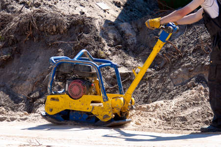 compacting: Worker at site Compacting a sand using a Plate Compactor