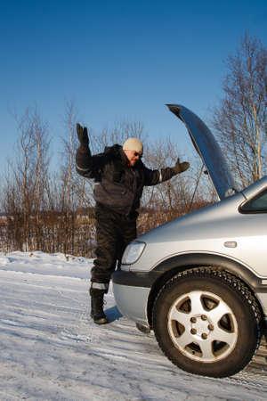 In cold winter day sad man looking at his broken car