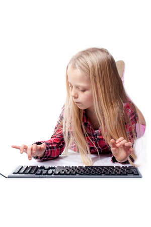 a little girl writes on the PC keyboard Stock Photo - 12640480